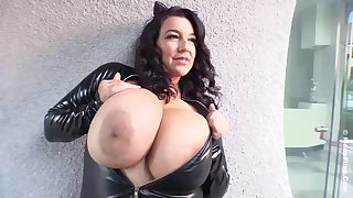 Busty brunette in a tight, latex costume, Subrina Lucia is showing us her massive milk jugs